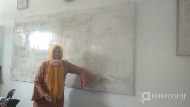 Kepala Sekolah SMPN 30 Padang Revianti Menunjukkan Pesan yang Ditinggal Pencuri di Papan Tulis