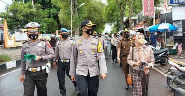 Kapolres Rohkmad didampingi Kasat Lantas M. Nasir dan Komisioner KPU Tanah Datar Fitri Yenti berjalan membagikan masker kepada pengunjung Pasar Batusangkar