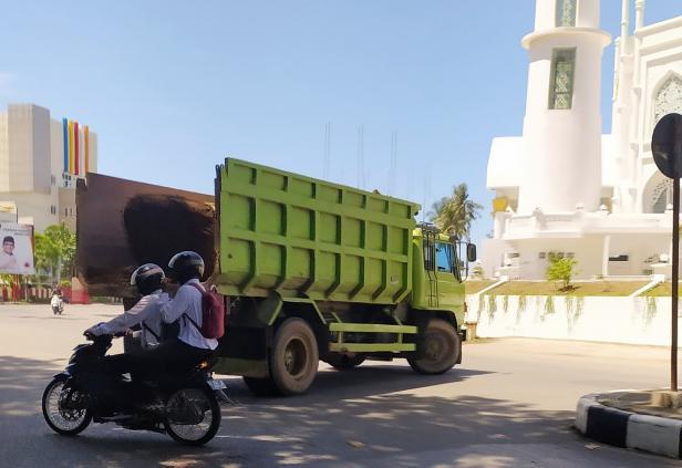 Truk bak terbuka bermuatan batu sampai di proyek penanganan abrasi pantai Masjid Al Hakim, Selasa, 17 Maret 2021