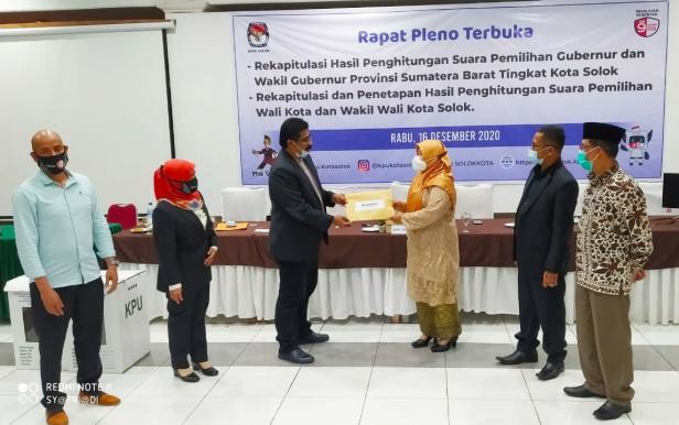 Ketua KPU Kota Solok, Asraf Dhanil menyerahkan hasil rekapitulasi suara kepada ketua Bawaslu kota Solok, Triati