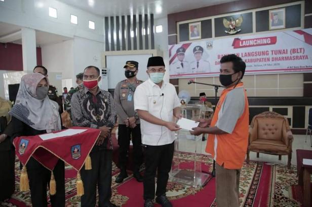 Bupati Dharmasraya Sutan Riska Tuanku Kerajaan menyerahkan BLT kepada masyarakat secaea simbolis, Selasa (19/5).