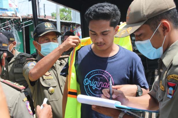 Petugas Satpol PP Padang memasangkan rompi kepada masyarakat yang melanggar Protokoler Kesehatan