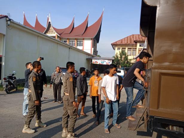 Belasan remaja yang berad di Mako Satpol PP Padang memasuki truk untuk diantarkan ke Dinas Sosial