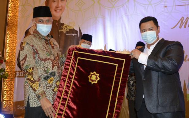 Pengusaha Minang Rifo Darma Saputra saat menyerahkan sajadah secara simbolis kepada Gubernur Sumbar Mahyeldi Ansharullah