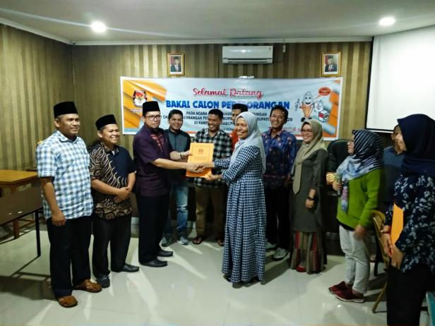 Pasangan Bacalon Bupati jalur Independen Hendra Syaputra-Mahyuzil serah terima berkas pendaftaran dengan ketua KPU, Ir. Gadis