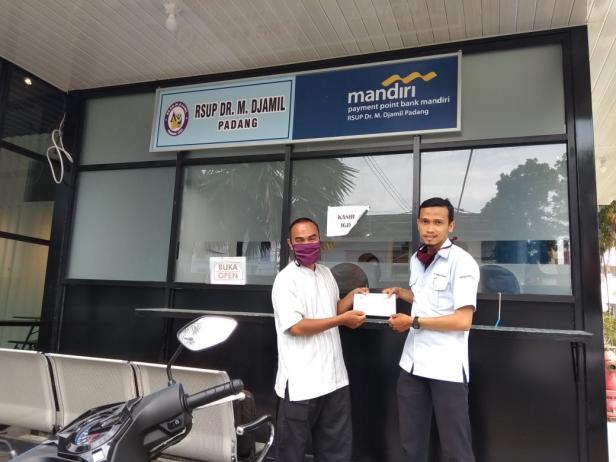 Petugas UPZ Baznas Semen Padang, Toni (kanan) menyerahkan bantuan uang tunai untuk bayar berobat bagi pasien kurang mampu.