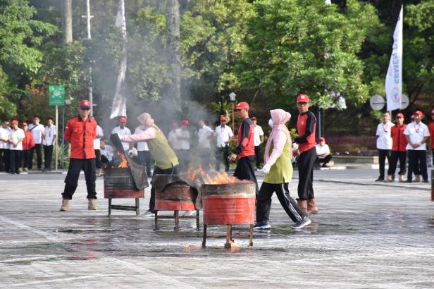 Ibu-ibu FKIKSP tengah melakukan simulasi pemadaman api di lapangan Plaza Kantor Pusat PT Semen Padang