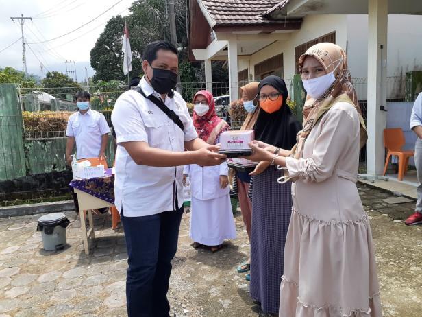 Staf Bina Lingkungan CSR Semen Padang menyerahkan bantuan makanan tambahan untuk ibu hamil di Kelurahan Limau Manis Selatan, Senin, (6/9/2021)