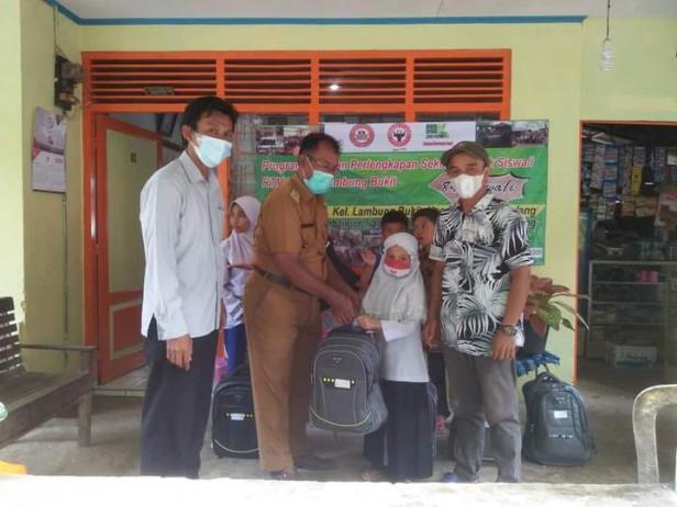 Lurah Lambung Bukit Yusrizal (dua dari kiri), menyerahkan bantuan paket pendidikan dari PT Semen Padang kepada salah satu pelajar dari RTM di Lambung Bukit.