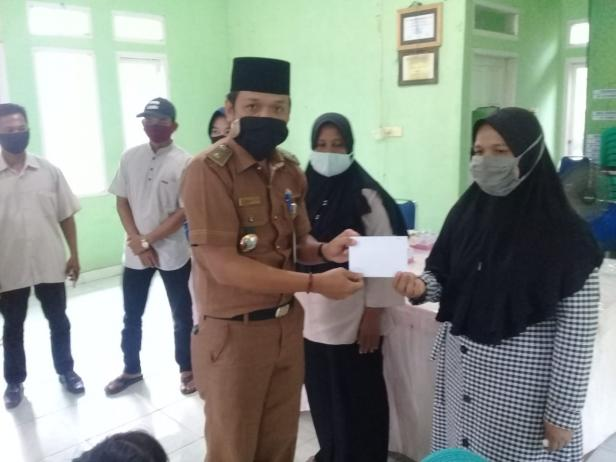 Lurah Bangsal Aceh Kecamatan Sungai Sembilan, Kota Dumai, Parlen Julianto menyerahkan bantuan beasiswa dari PT Semen Padang kepada perwakilan orangtua atau walimurid penerima beasiswa, di Kantor Lurah setempat, Selasa (1/9/2020).