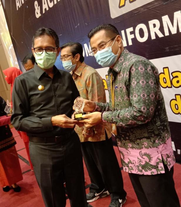 Gubernur Sumbar Irwan Prayitno (kiri) menyerahkan penghargaan tokoh keterbukaan informasi publik kepada Direktur PNP Surfa Yondri.