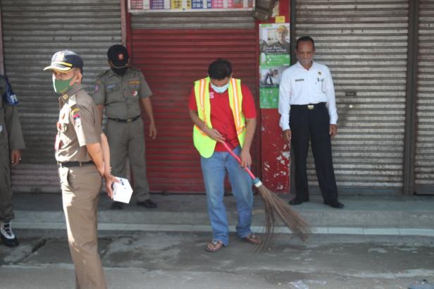 Pedagang yang tidak menggunakan masker sedang menyapu jalan