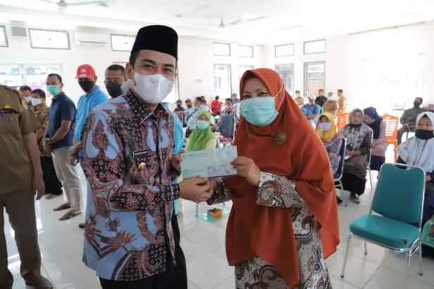Wakil Wali Kota Solok, Dr. Ramadhani Kirana Putra menyerahkan kepesertaan BPJS Kesehatan pada peserta sosialisasi