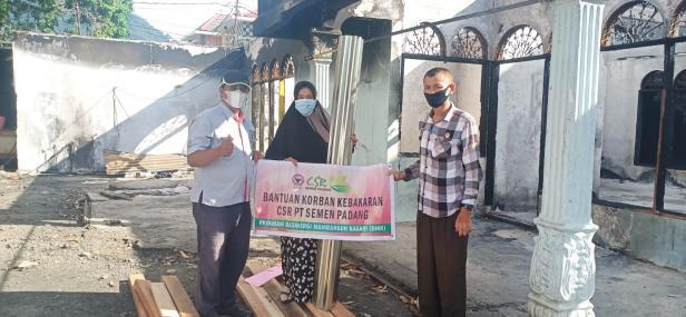 Staf CSR Semen Padang Yaldi (kiri) disaksikan Lurah Kampung Baru Nan XX Afrianos (kanan), menyerahkan bantuan kepada Armaini (tengah) korban kebakaran di Jalan Ampera.