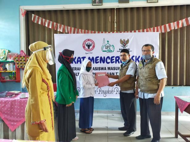 Kepala Pelaksana Harian UPZ Baznas Semen Padang Muhammad Arif menyerahkan bantuan pendidikan berupa biaya masuk sekolah secara simbolis.
