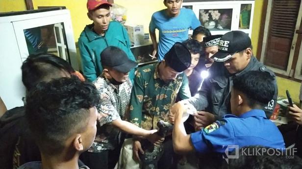 Petugas mengamankan seekor ular Piton sepanjang 4 meter dari dalam rumah warga di Koto Kaciak, Muaro Paneh