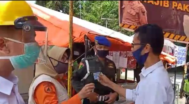 Ketua KPU Sumbar Saat Menyerahkan KTP ke Petugas Posko COVID-19 di Lubuk Peraku