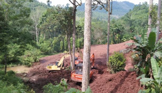 Alat berat sedang mengeruk material longsor proyek instalasi pengolahan air di Tapan
