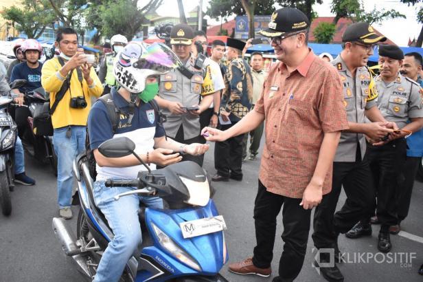 Riza Falepi saat membagikan hand sanitizer kepada pengguna jalan di depan Posto Tanggap Darurat Covid-19 Payakumbuh.