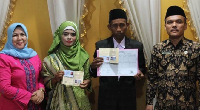 Pasangan pengantin baru di Payakumbuh saat menerima dokumen kependudukan baru.