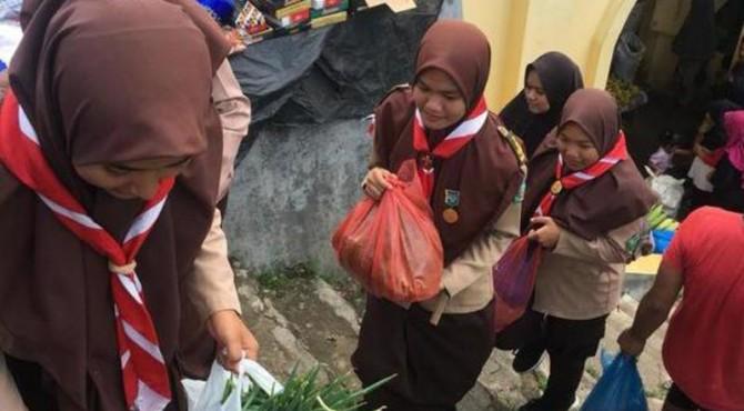 Satgas Pramuka Penegak Saat Mengangkat Barang Belanjaan Ibu-ibu di Pasar Tradisional Sawahlunto