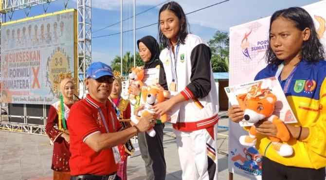 Kepala Bidang Humas KONI Sumbar Sareng Suprapto mengalunhkan medali emas kepada Serena Karmelita
