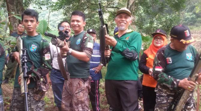 Joko Ade Saputra (dua dari kiri) memegang senapan angin berfoto bersama dengan Walikota Padang, Mahyeldi Ansharullah (tiga dari kiri) disela-sela berburu hama wereng di kawasan perbukitan di Kota Padang beberapa waktu lalu.
