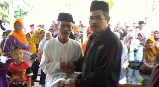 Ketua Harian LAZ Semen Padang Muhammad Arif menyerahkan bantuan rutin dan oleh-oleh Ramadan kepada salah seorang jompo