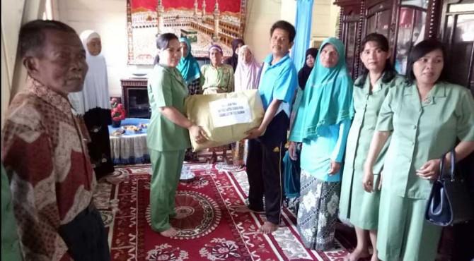 Ketua Persit Kodim 0305/Pasaman, Ny. Lusia Cosmas Pramundhito,SH menyerahkan bingkisan kepada masyarakat miskin di Bonjol dan Lubuk Sikaping Kabupaten Pasaman.