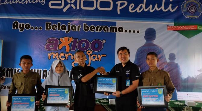 Direktur Axioo Class Program sedang memberikan plakat pemberian beasiswa kepada para siswa SMK Muhammadiyah Rembang yang diterima oleh Kepala Sekolah SMK Muhammadiyah Rembang