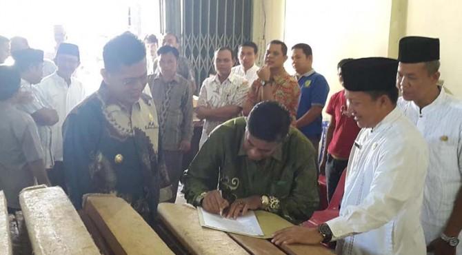 Salah seorang penerima bantuan kayu menandatangani berita acara penyerahan bantuan disaksikan Wabup Pasaman, Atos Pratama dan Kadis Kehutanan, Yozarwardi dan Dandim 0305 Pasaman, Cosmas Pramundhito.