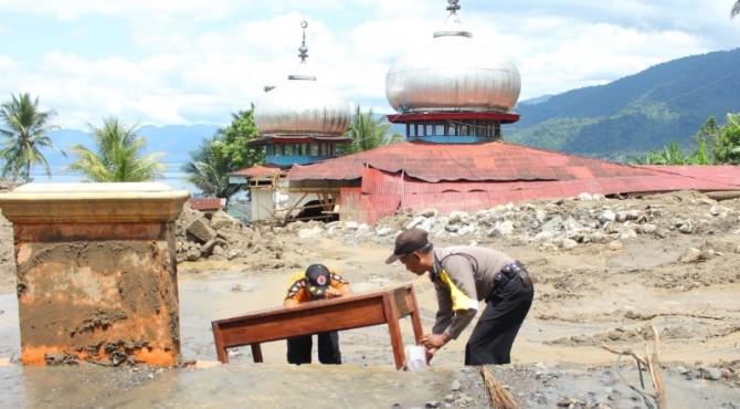 Polisi dan personel membersihkan kursi MDTA yang dihantam banjir bandang