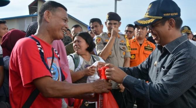 Wakil Bupati Kepulauan Mentawai, Kortanius Sabeleake (kanan) menyerahkan goody bag berisi baju, topi, snack dan obat-obatan secara simbolis kepada peserta Mudik Gratis Bersama BUMN di Dermaga TuaPejat