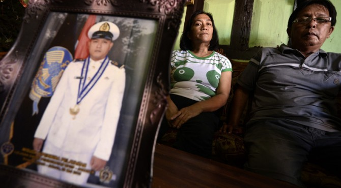Keluarga WNI yang disandera kelompok Abu Sayyaf, Agustin Pilohoma (50) dan Jemmy Repi (58) duduk di belakang foto putranya, Alfian Elvis Repi, di kediaman mereka di Desa Kauditan, Minahasa Utara, Sulawesi Utara, Rabu (6/4).
