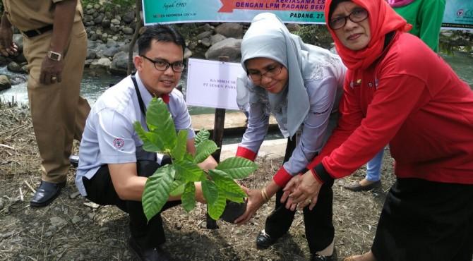Staf CSR Semen Padang, Alfred Rusli (kiri) bersama Kepala Bidang DikkessosLH CSR Semen Padang secara simbolis menanam bibit Kakao di rumah warga di Padang Besi
