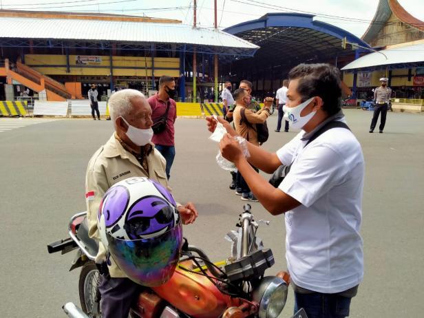 Ketua Balai Wartawan Luak Limopuluah, Afridel Ilham menyerahkan masker gratis kepada pengguna jalan di Kota Payakumbuh, Rabu (16/9).