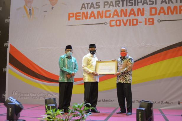 Kepala Departemen Komunikasi & Hukum Perusahaan PT Semen Padang Oktoweri (kanan) menerima penghargaan daei Walikota Padang Mahyeldi Ansharullah.