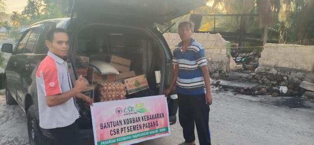 Petugas dari CSR Semen Padang (kiri) menyerahkan bantuan paket sembako kepada Darwas, korban kebakaran di Batu Gadang Padang, Senin (19/4/2021)