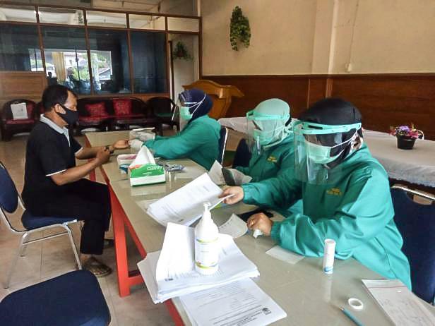 Petugas kesehatan melakukan pemeriksaan kepada masyarakat yang akan menjadi petugas tempat pemungutan suara.