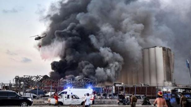 Sebuah helikopter memadamkan api di lokasi ledakan di pelabuhan kota di Beirut, Lebanon, Selasa (4/8)