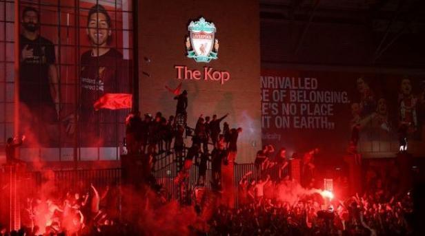 Suporter merayakan keberhasilan Liverpool menjadi juara Liga Inggris 2019/2020 di luar Anfield di Liverpool, Inggris, 25 Juni 2020.