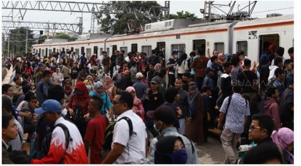 Rangkaian kereta rel listrik (KRL) menaikkan dan menurunkan penumpang