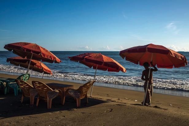 Seorang pedagang mempersiapkan tenda di kawasan wisata pantai Padang