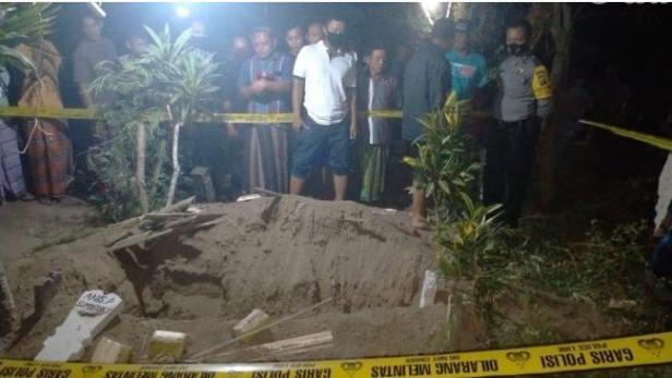 Warga dan kepolisian sedang melihat kondisi makam yang digali orang misterius di Ngoro, Jombang, Minggu (20/09/2020)