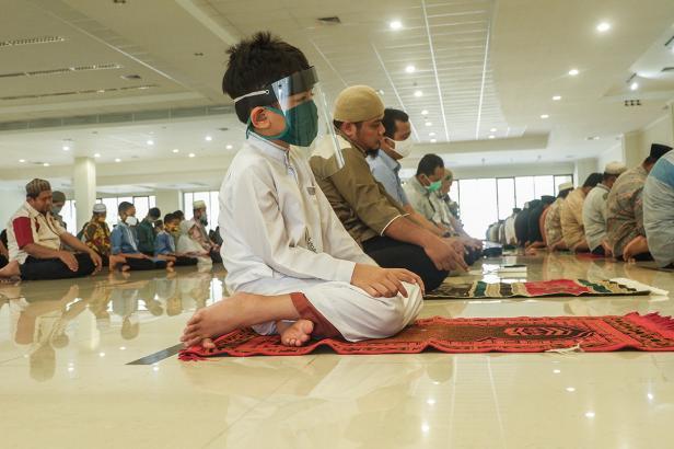 Seorang anak mengenakan masker dan faceshield saat melakukan salat