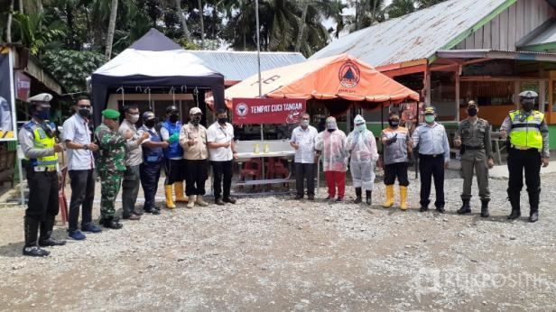 Staf Humas PT Semen Padang Jon Reflus foto bersama dengan petugas Pos Check Point di Bungus Teluk Kabung usai menyerahkan bantuan fasilitas cuci tangan.