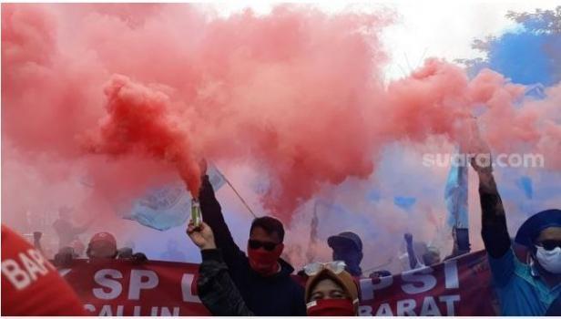 Massa buruh menyalakan bomb smoke saat aksi menolak UU Cipta Kerja di kawasan Patung Kuda.