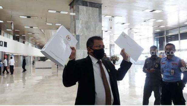 Sekjen DPR RI Indra Iskandar menunjukkan draf final UU Cipta Kerja saat hendak bertolak ke kantor Setneg, Rabu (14/10/2020).