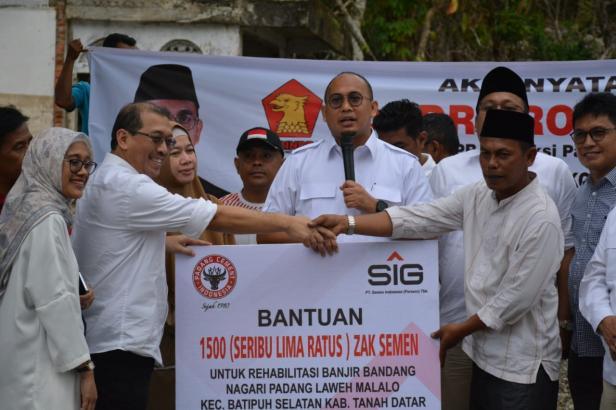 Direktur Keuangan PT Semen Padang Tubagus Muhammad Dharury (kiri) menyerahkan secara simbolis bantuan semen sebanyak 1500 zak kepada Wali Nagari Padang Laweh Malalo, Akhiari, yang disaksikan anggota DPR RI Andre Rosiade (tengah).