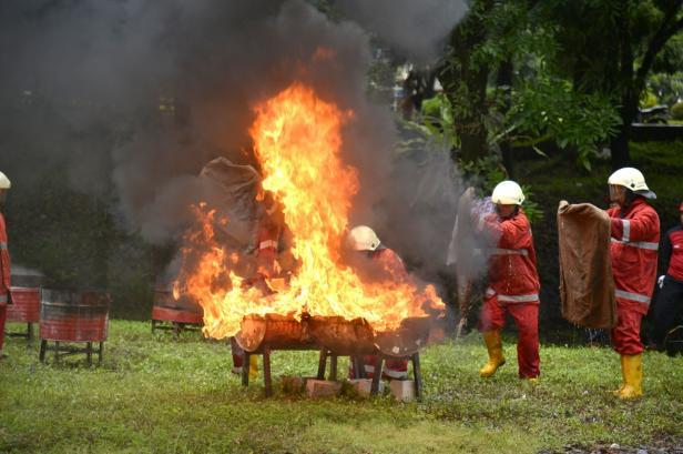 Peserta lomba HSE Challange tengah memadamkan kobaran api menggunakan karung goni.